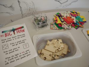 flyer, plain jigsaw pieces and coloured-in jigsaw pieces on a table