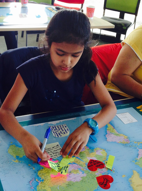 Schoolgirl putting post-it notes on a map