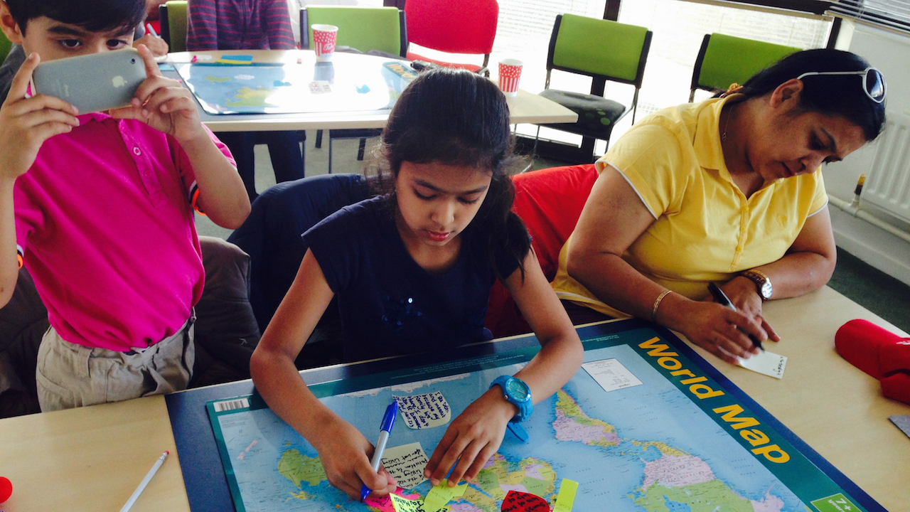 Schoolgirls putting post-it notes on a map